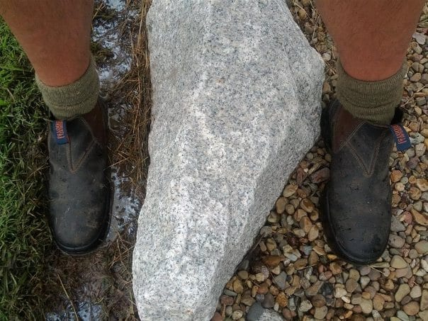 One boot in mud and the other on a gravel path showing the difference