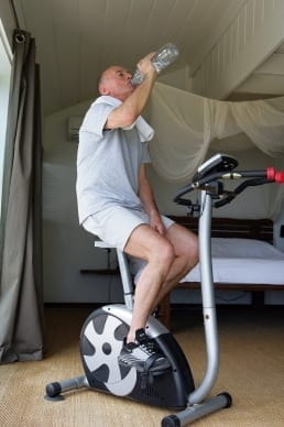 Mature Man on Exercise Bike at Home