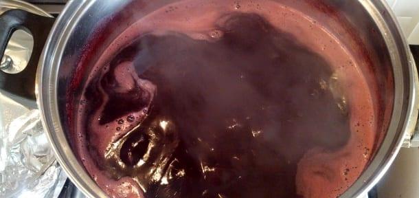 Rosella jam syrup simmering after sugar added